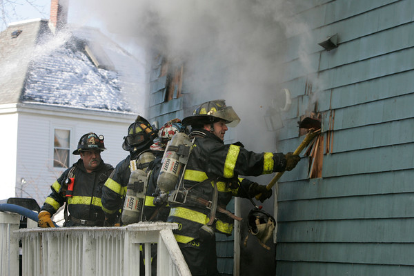 Swampscott:<br /> Firefighters use an ax to access the fire in the walls on the side of the house at the scene of the fire at 50 Andrew Road in Swampscott.<br /> Photo by Ken Yuszkus/The Salem News, Thursday, January 3, 2013.
