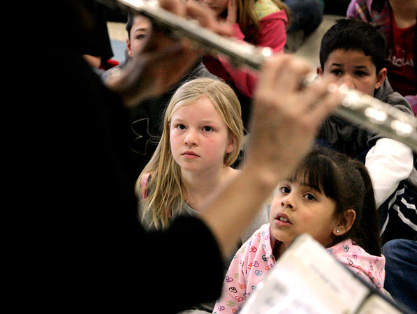 Beverly:<br /> Mackenzie Gilligan, left, Bianca Fernandez, right, and Jackson McGinn in back, listen to Stephanie Stathos play the flute during the Cape Ann Symphony presentation to introduce the orchestra and instruments to the 4th and 5th grades at the Cove School .<br /> Photo by Ken Yuszkus/The Salem News, Tuesday, January 29, 2013.