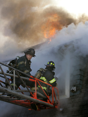 Swampscott:<br /> Firefighters fight the fire through a second story window at the scene of the fire at 50 Andrew Road in Swampscott.<br /> Photo by Ken Yuszkus/The Salem News, Thursday, January 3, 2013.
