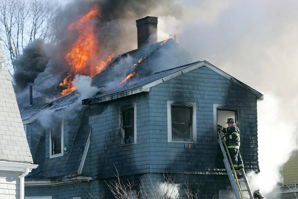 Swampscott:<br /> Firefighters fight the fire through a second story window in the back of 50 Andrew Road in Swampscott.<br /> Photo by Ken Yuszkus/The Salem News, Thursday, January 3, 2013.
