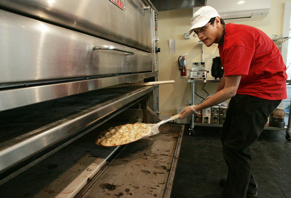 Wenham:<br /> Max Sklar removes a pizza from the oven at the new Mangia Pizzeria in Wenham.<br /> Photo by Ken Yuszkus/The Salem News, Thursday, January 17, 2013.