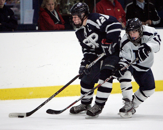 Peabody:<br /> St. John's Prep Derek Osbahr, left, has control of the puck, but Peabody's Bobby Caproni, right, is intent on stealing it during the St. John's Prep at Peabody hockey game.<br /> Photo by Ken Yuszkus/The Salem News, Monday, January 14, 2013.