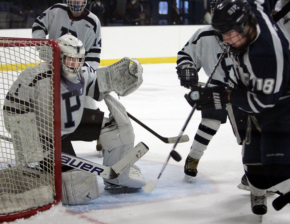 Peabody:<br /> Peabody's goalie Stephen Ferrante keeps an eye on the puck as St. John's Prep Bryan Uva bats the puck downward in front of the net during the St. John's Prep at Peabody hockey game.<br /> Photo by Ken Yuszkus/The Salem News, Monday, January 14, 2013.