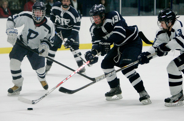 Peabody:<br /> With Peabody's Cam Smullen, left, and Peabody's Giuseppe Zarro, right, St. John's Prep Paul Crehan heads toward the goal during the St. John's Prep at Peabody hockey game.<br /> Photo by Ken Yuszkus/The Salem News, Monday, January 14, 2013.