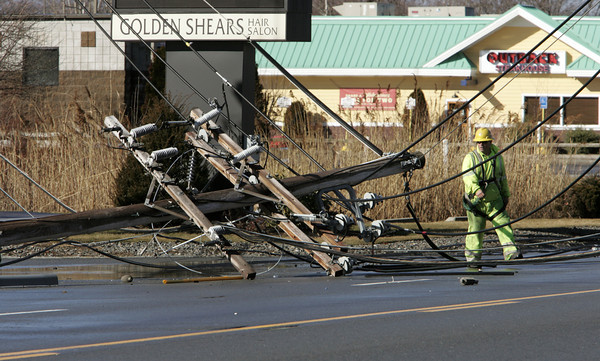 Peabody:<br /> A workman walks by the snapped off top of one of the fallen utility poles on Route 114.<br /> Photo by Ken Yuszkus/The Salem News, Thursday, January 31, 2013.