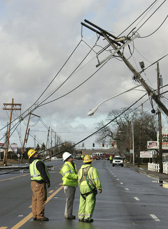 Peabody:<br /> Workmen view one of the tilting utility poles on Route 114.<br /> Photo by Ken Yuszkus/The Salem News, Thursday, January 31, 2013.