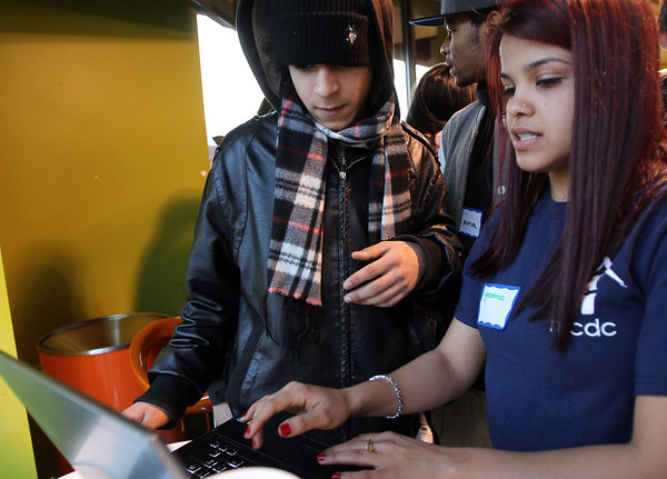 Salem: Andres Munoz, 17, of Salem, left, gets help from Yesenia Velez, 20, from North Shore CDC, to sign up for the Point Neighborhood Community PlanIt Game. The video game launched on Monday and runs for three weeks, allowing Point residents to give input on important matters in their neighborhood. There was a launch party at Orange Leaf on Friday afternoon, Jan. 25. David Le/Salem News