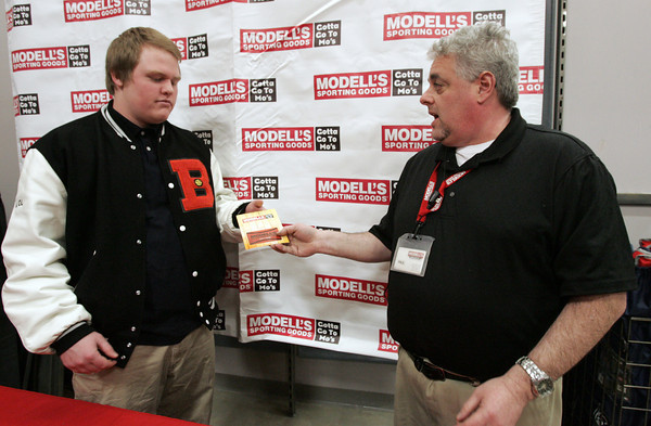 Beverly:<br /> Kevin Kennedy, left, of the Beverly football team receives a $20 gift certificate and coupons from Paul Millman who is the acting store manager of Modell's Sporting Goods store.<br /> Photo by Ken Yuszkus/The Salem News, Friday, January 18, 2013.