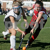 Beverly: Beverly High's Julie Crowley battles for the ball against Waltham's Brianna Sorrentino in the first half, during the Division 1 North field hockey state tournament. Photo by Mark Lorenz/Salem News