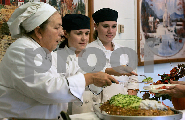 Danvers: Chef Denise Graffeo teaches Katie Barry and Meghan Rice, both students at North Shore Community College Culinary Arts program on  how to cut and serve during culinary arts class at Essex Aggie. Photo by Mark Lorenz/Salem News