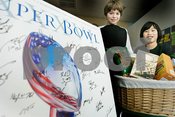 Salem: Fourth-grader Jonathan Chefitz, left, and  Leo Santoro, a fifth-grader with some of the auction items at the Phoenix School. Photo by Mark Lorenz/Salem News