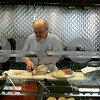 """Danvers: Kyriakos """" Kary """" Andrinopoulos slices meat for customers during lunch time at his restaurant, New Brothers Restaurant & Deli. Photo by Mark Lorenz/Salem News"""