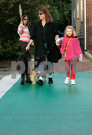 Salem: Kathleen Hoff and her daughter, Satya, 7,  use the cross walk in front of the Saltonstall School. There has been many close calls in the area with cars not stopping for pedestrians. With them are Penny and Anakin. Photo by Mark Lorenz/Salem News
