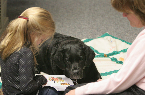Swampscott: Kenzie Mclaren reads at the Swampscott Library to Merry, during reading to dogs to help kids be more relaxed while reading out loud. Merry's owner, Donna Carmondy sits with them. Photo by Mark Lorenz