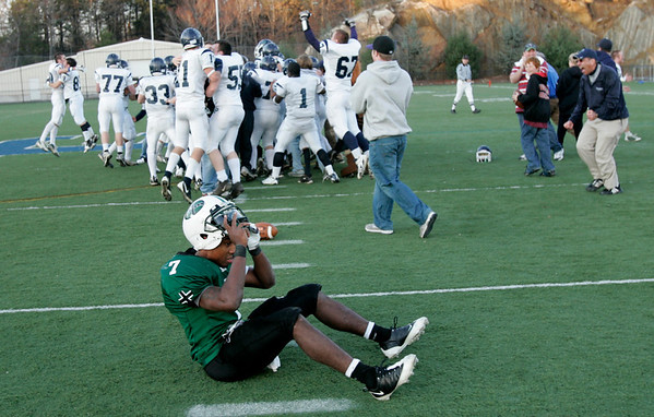 Beverly: Brooks School Jordan Johnson sits in disappointment as Pingree School players celebrate their 7-6 victory. Pingree scored with 40 seconds left in the game in the Clark/Francis Bowl as part of NEPSAC playoffs, played at Endicott College. Pingree defeated Brooks 7-6. Staff by/Mark Lorenz