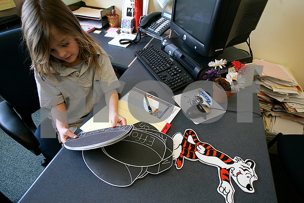 Peabody: Second grade student, Kathryn DiGiulio,8, who is principal for the day at the Carroll School sorts through hockey pucks, with sayings on them. They will be part of a billboard she is making with principal Cara Murtagh. Photo by Mark Lorenz/Salem News