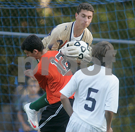 Danvers: St. Johns Prep keeper Adam Colella grabs this kick as Beverly High's Brad Surette collides with him, in the first half of play, at St. John's Prep. Photo by Mark Lorenz/Salem News