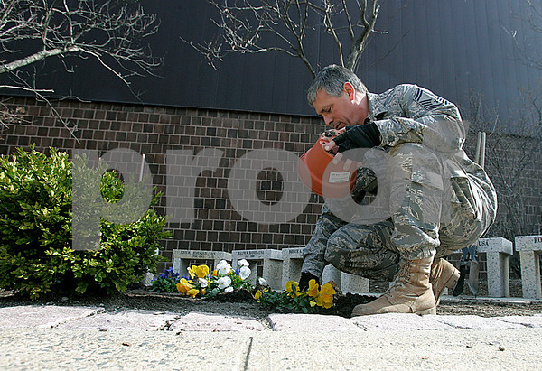 Peabody: SMSgt. Keith Kremer,Peabody High School's JROTC instructor works on planting flowers in front of the school. Photo by Mark Lorenz/Salem News