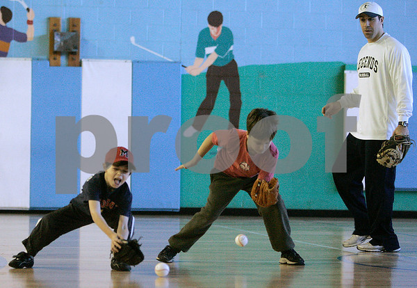 Marblehead: Steve Lomasney watches Maxwell Mogolesko, left, and Alexander Perkins try to catch these balls, during a baseball clinic at the Marblehead Jewish Community Center. Photo Mark Lorenz/Salem News