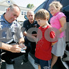 Hamilton: Det. Stephen Trepanier of the Hamilton Police Department with Skip Mullin, Hamilton fire fighter/EMT give out ice-cream citations to Harry Sostek and his sister Nadia. The two departments are rewarding kids with these citations for wearing seatbelts, biking helmets, walking there bikes across the road, using cross walks.  The Sostek's were with their mother Page. Photo by Mark Lorenz/Salem News August 22, 2008.