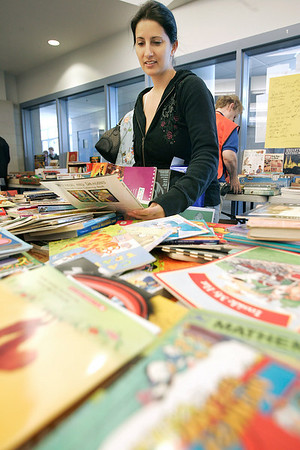 Danvers: Gina Girard of Peabody looks through books at one of many tables with items for sale, during Operation Troop Support. The annual yard sale was held at the Holten Richmond Middle School. Photo by Mark Lorenz/Salem News