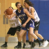 Peabody: Danvers High School basketball player, Kellie Macdonald looks to pass as Bishop Fenwick's Kate Lipka (33) and Sarah James (10) try to box her in. Photo by Mark Lorenz/Salem News