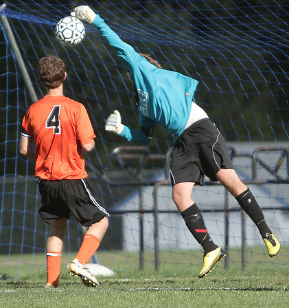 Peabody: Beverly High Schools keeper Pat Wilson knocks down this shot by a Beverly player during game. Beverly player, Josh Carmer keeps back. Photo by Mark Lorenz/Salem News