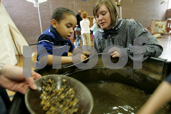 Peabody: Burke School kindergartner student, Dante Olowu looks for gold with the help of Kristine Peterson Northeast Tour Leader for the Tin Cup Adventures. Students learned the ways of pioneer living with hands-on experience. Photo by Mark Lorenz/Salem News