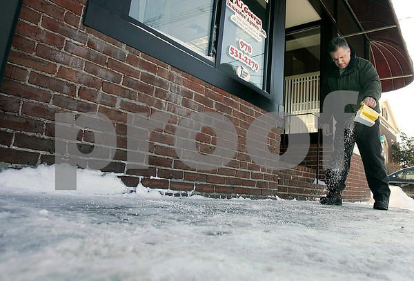 Peabody: Peter George, president of AJ George Insurance Agency, Inc., puts rock salt down in front of his Foster Street business. Photo by Mark Lorenz/Salem News