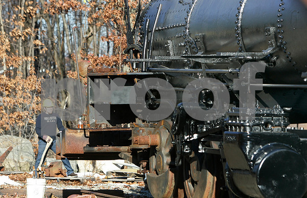Peabody: Kevin Nairn, volunteer for the Connecticut Vallery Railroad, works on the old steam engine located at the Peabody Public Works. A crew began the process of dismantling the engine which will be hauled to Essex, CT. Photo by Mark Lorenz/Salem News