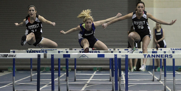 Peabody: Beverly's Hayley Carlotto (left) took second as her teammate, Taylor Manzi (right) took first place, out doing Peabody's Kirsten Nihan in the 45m hurdles in meet. Photo by Mark Lorenz/Salem News
