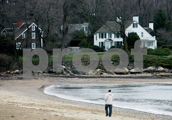 Beverly: Despite the cold and rain, a walker enjoys the quietness of Dane Street Beach, early Saturday morning. Photo by Mark Lorenz/Salem News