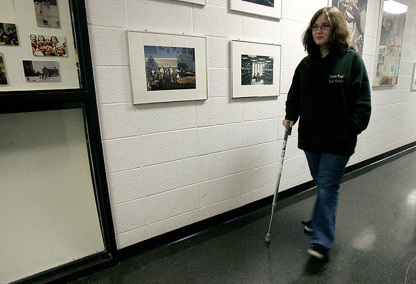 North Andover: Sam Mattei of Salem, a Merrimack College student, walks in the media center, where she works, was injured in the MBTA crash in Boston, now back at school, but is still suffering problems. Photo by Mark Lorenz/Salem News