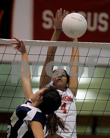Salem: Salem High School's Stella Gutierrez blocks a shot against Malden's Eva Chan in their first set. Photo by Mark Lorenz/Salem News