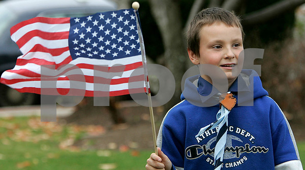 Beverly: Derek Graham,8, who is a member of the Boy Scouts Troop 2 out of Beverly, holds his flag before the start of the Beverly Veterans Day serive yesterday morning, held at Odell Park. Staff by/ Mark Lorenz