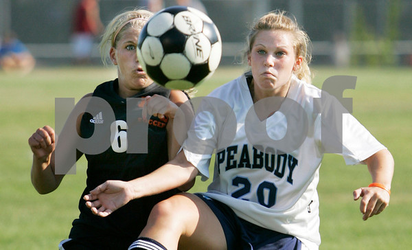 Peabody:  Beverly High School's Kayla Deady battles for the ball against Peabody High School's Caitlyn Pinkham in the first half of play at Peabody High School. Photo by Mark Lorenz/Salem News.