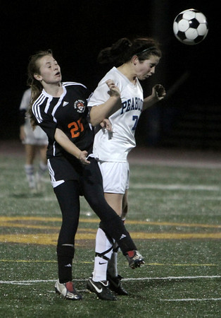 Peabody: Peabody High's Angela Ellison heads the ball against Newton North's Christina Callahan, in playoff game at Bishop Fenwick High School. Photo by Mark Lorenz/Salem News