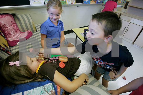 Danvers: Anthony Moscato and Avery Scharffenberg, using pretend food play around with their classmate Hannah Golden in Katie Pelletier's class at the Thorpe School.Kindergartners are now going a ful day. Photo by Mark Lorenz/Salem News