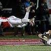 Lowell: Masconomet Regional High School Chris Splinter dives in for a touchdown against Concord-Carlisle Eric DeBruzzi in the first half of play. Photo by Mark Lorenz/Salem News
