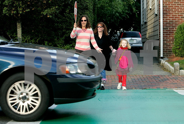 Salem: Amy Lypps a crossing guard volunteer watches as a car does not stop for her while Kathleen Hoff and her daughter, Satya ,7,  try crossing in front of the Saltonstall School. Photo by Mark Lorenz/Salem News.