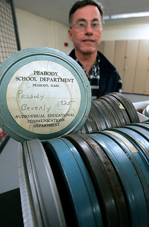 Peabody: Phil Sheridan Peabody High School's athletic director with vintage 16 mm football game tapes dating back to 1935. The school would like to have the tapes put on DVD. Photo by Mark Lorenz/Salem News