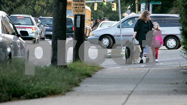 Salem: Kathleen Hoff and her daughter, Satya, 7,  walk along Lafeyatte on their way to Saltonstall School with Penny and a friends pet, Anakin.  There have been many close calls with cars not stopping for pedestrians in the cross walks. Photo by Mark Lorenz/Salem News