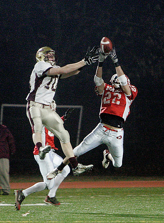 Lowell: Masconomet Regional High School Evan Bunker almost grabs an interception against Concord-Carlisle Bumpus John. Photo by Mark Lorenz/Salem News