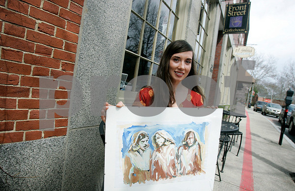 Salem: Elayne McCabe, shows off a piece of art work by artist, Malik Sajad. His work will be on display at the Front Street Coffeehouse for the month of May. Photo by Mark Lorenz/Salem News
