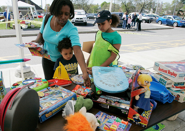 Danvers: Kim Locke and two of her three children, Jordan, 4 and Sydney, 8 of Danvers pick out toys at one of the tables,  during Operation Troop Support. The annual yard sale was held at the Holten Richmond Middle School. Photo by Mark Lorenz/Salem News