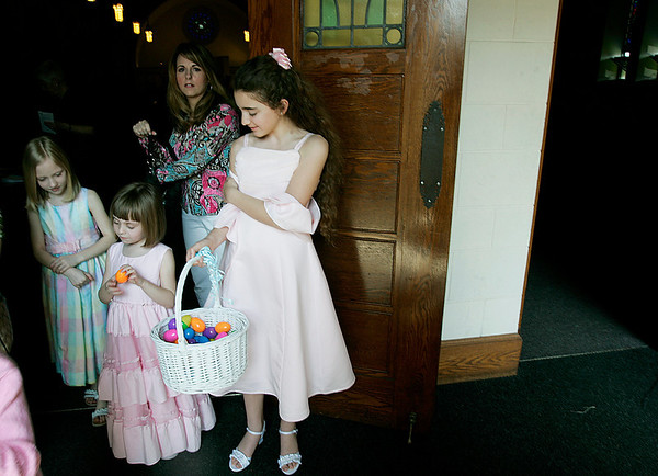 Danvers: Rachel Butler hands at Easter eggs after mass at, St Mary of The Annunciation Parish to Jacqelyn Jones and her sister, Sommerlyn, with them is their mother, Jennifer of Danvers. Photo by Mark Lorenz/Salem News