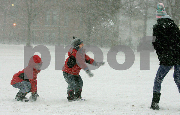 Salem: Twin brothers, Nate and Tyler Gold, 4, play on the Salem Common with their baby sitter, Christine Greenwood, during yesterday's snow fall. Photo by Mark Lorenz/Salem News
