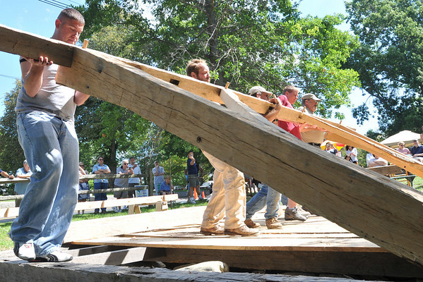 Ipswich: Kevin Tedesco, left, Jesse Brown, Tim Chouinard, Jordan Swenton, and Bob Spoerl raise the broad side of a re-creation timber frame house from 1657 as described in Ipswich town records.  photo by Mark Teiwes / Salem News