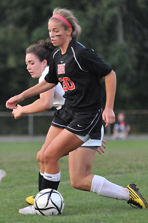 Danvers:  North Andover's Leah Chittick dribbles the ball followed by Danvers player Kylie Plaza during Tuesday's 0-2 loss to Danvers.  photo by Mark Teiwes / Salem News