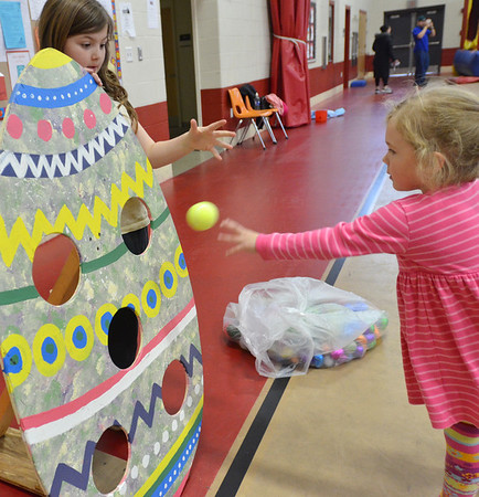 Salem:  Jillian Sholds, 9, left, watches as Annika Savage, 4, attempts a close range shot at a game during the Mayor's annual Easter egg event.  photo by Mark Teiwes